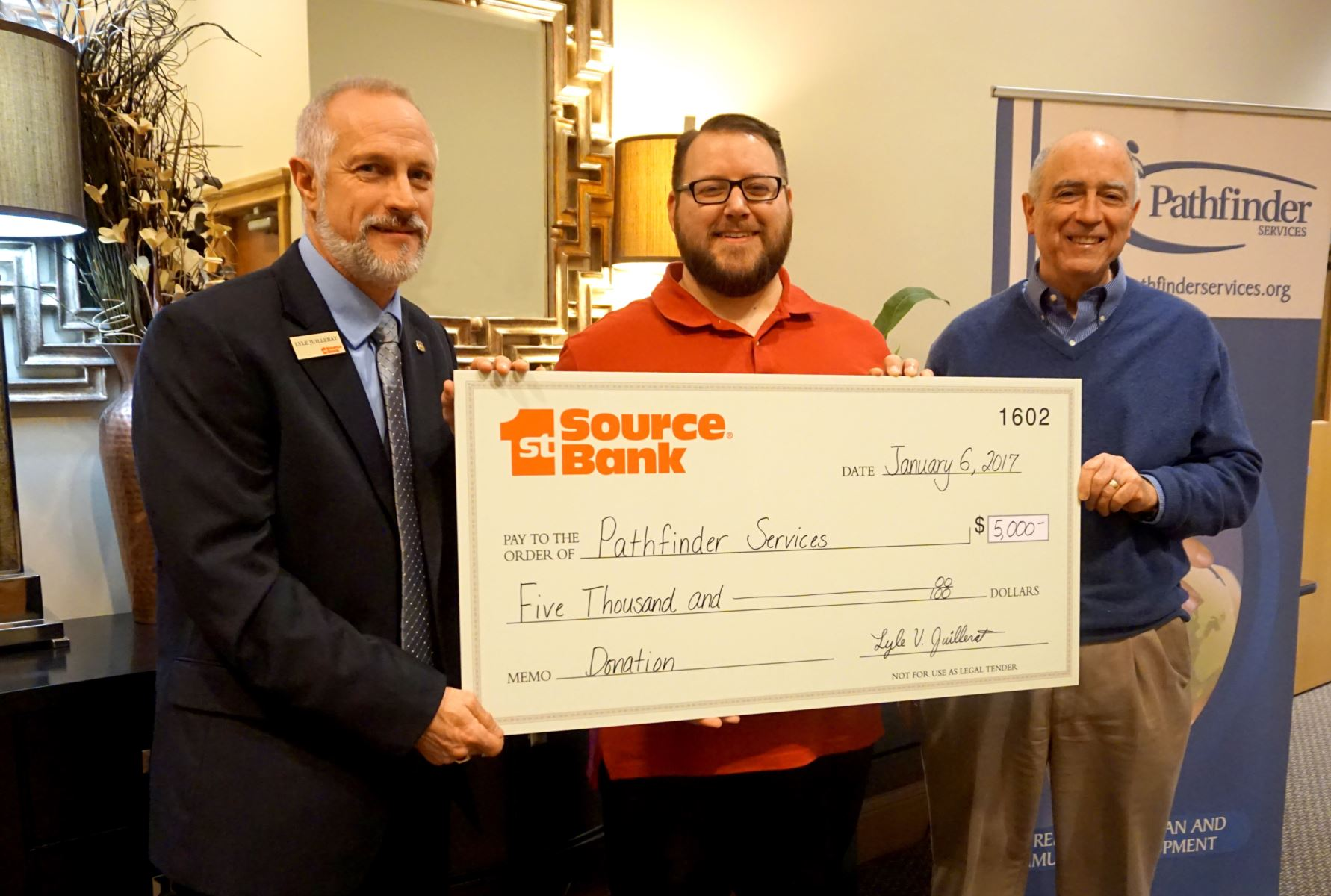 Lyle Juillerat (far left) presents donation to Justin Barker and John Niederman of Pathfinder Services.