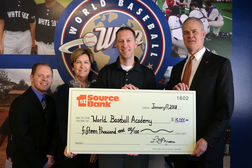 World Baseball Academy representatives receive $15,000 check from 1st Source Bank for new scoreboard.